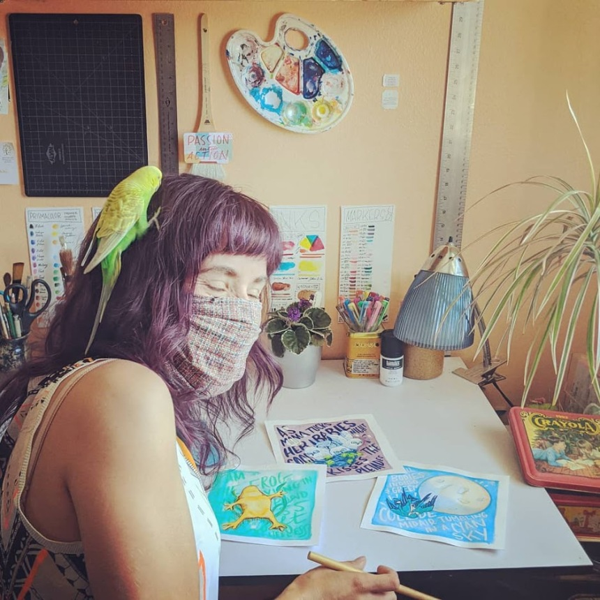 Django, my blind green bird friend, climbing up my head in the art studio like it was the presidential challenge in front of my drafting table with painted pieces on it.