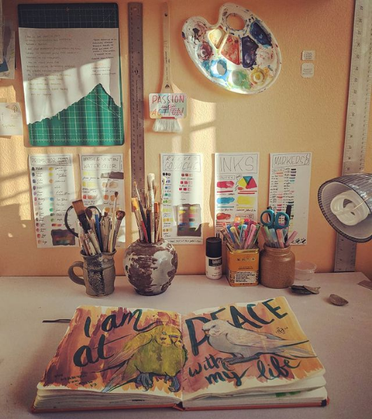 Photo of a sketchbook open on my drafting table with art supplies behind it