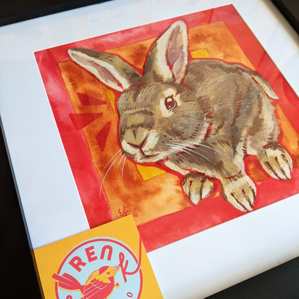 Portrait of a painted bunny in a frame with a yellow business card from Ren S.K. Studio