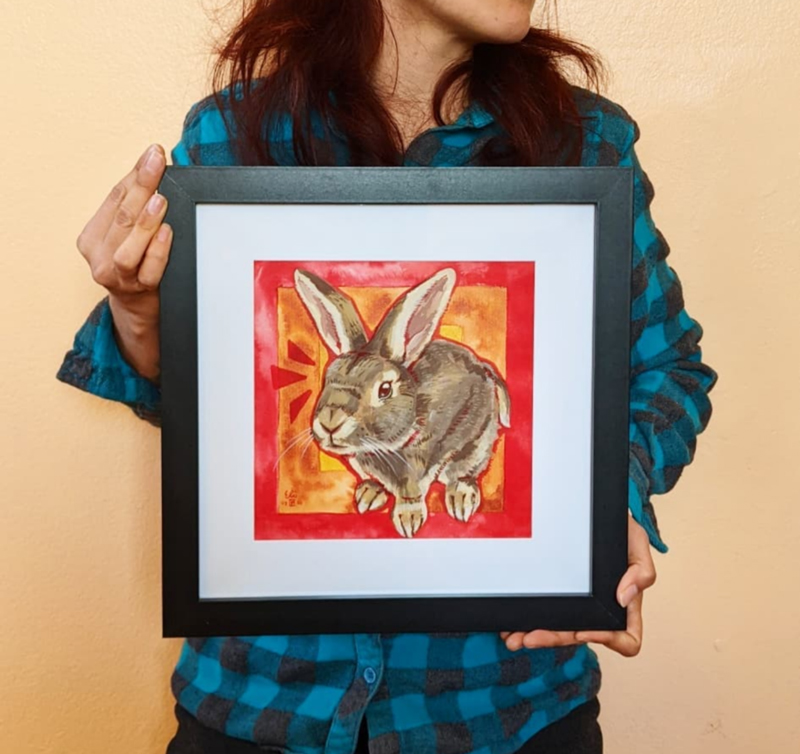 Artist holding a framed portrait of a bunny