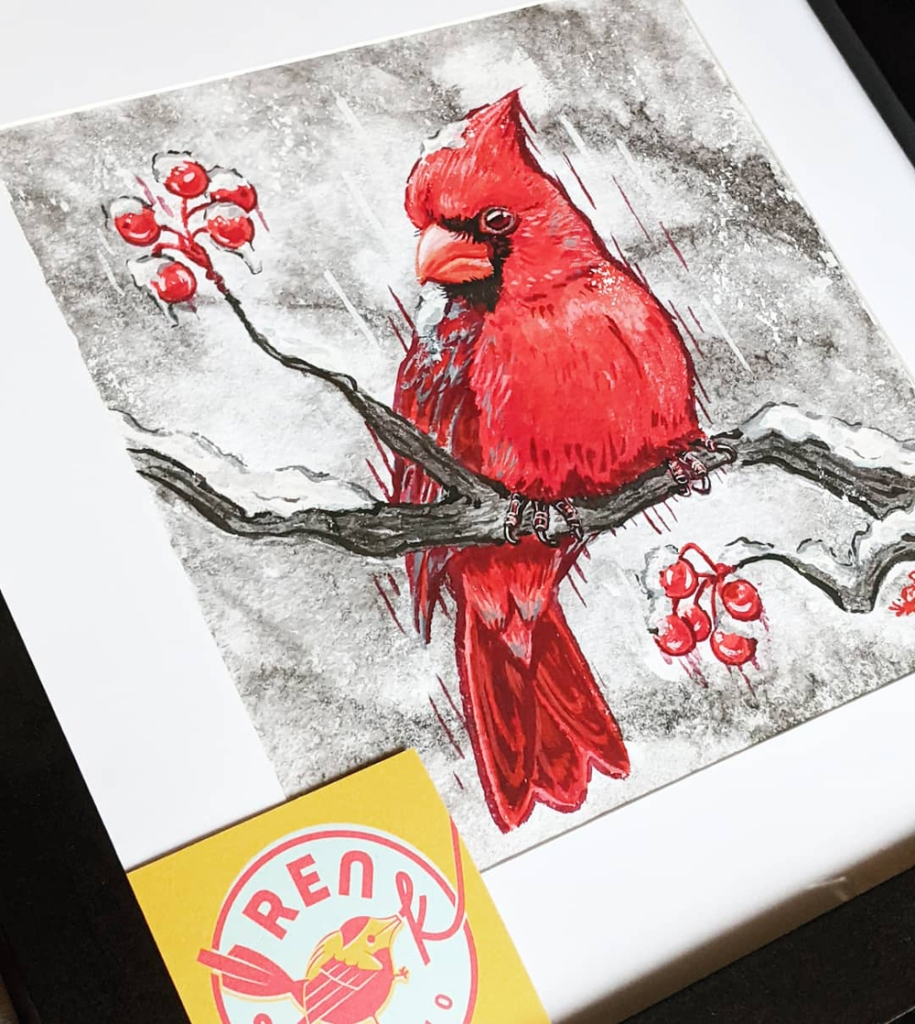 framed portrait of a northern cardinal painted in gouache and sumi ink, yellow Ren S.K. Studio business card in the bottom corner.