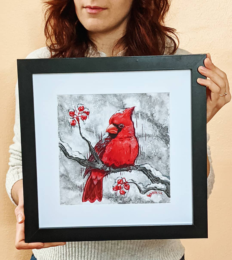 artist holding a framed portrait of a northern cardinal painted in gouache and sumi ink