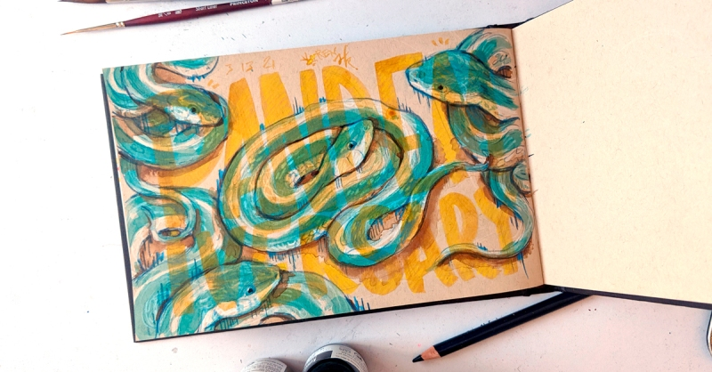 """Sketchbook open to a drawing of four garner snakes in colored pencil and ink. Hand-lettering over it in transparent ochre ink says """"PANDEMIVERSARY"""""""