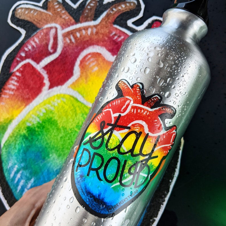 """Pride rainbow sticker on a water bottle, heart shaped that say """"Stay Proud"""""""